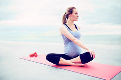 Pregnant young woman doing fitness exercises Royalty Free Stock Images