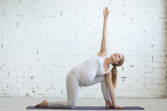 Pregnant young woman doing prenatal extended side angle yoga pos Royalty Free Stock Images