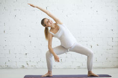 Pregnant young woman doing prenatal yoga. Goddess pose with side Royalty Free Stock Photography