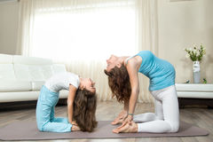 Pregnant young woman doing prenatal yoga with her little daughte Royalty Free Stock Photo