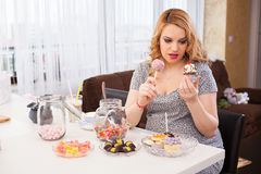 Pregnant young woman eating sweets royalty free stock photos