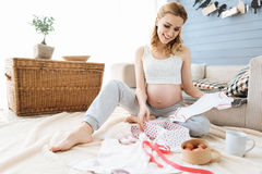 Pregnant young woman enjoying new baby clothes royalty free stock photography