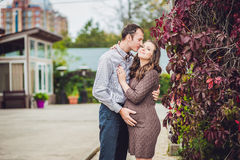 A pregnant young woman and her husband. A happy family standing at the red autumn hedge, holding belly. pregnant woman relaxing in Royalty Free Stock Images