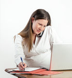 Pregnant Young Woman on Phone at Laptop at Office  Royalty Free Stock Images