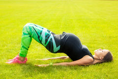 The pregnant young woman. Plays sports on a grass Stock Photos
