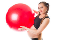 Pregnant  young woman and red fitness ball. On white background. The concept of Sport and Health Stock Photography