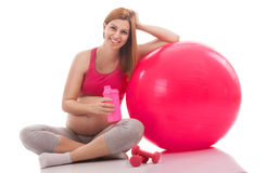 Pregnant young woman relaxing after training with drink and ball Royalty Free Stock Images
