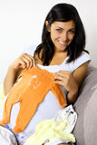 Pregnant young woman showing baby clothes Stock Photography