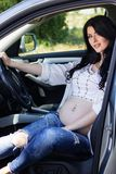 Pregnant young woman is sitting in car Stock Images