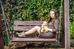 A pregnant young woman sitting on a swing, with a teddy bear. pregnant woman relaxing in the park. Stock Image