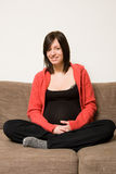 Pregnant young woman on sofa Stock Photography
