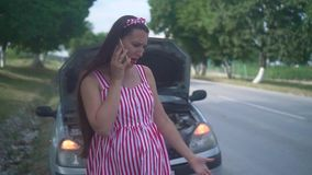 A pregnant young woman stands near a wrecked car on a rural road. Upset girl calls on the phone and asks for help. A pregnant young woman stands near a wrecked stock footage