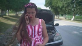 A pregnant young woman stands near a wrecked car on a rural road. Upset girl calls on the phone and asks for help. stock video