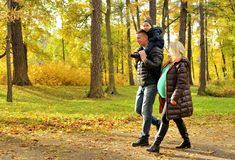 Pregnant young woman walking in autumn park with her husband and child Stock Photos