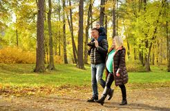 Pregnant young woman walking in autumn park with her husband and child Royalty Free Stock Photos