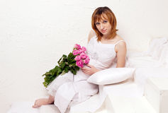 The pregnant young woman in a white dress with union of roses Royalty Free Stock Images