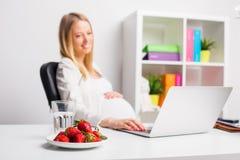 Pregnat妇女在食用的办公室草莓 库存图片