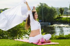 Pregnat woman holding white fabric on wind. Beautiful young pregnat woman holding white fabric on wind siting in lotus position Stock Photography