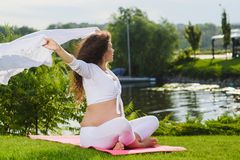 Pregnat woman holding white fabric on wind. Sport, fitness, healthy life during pregnancy. Beautiful young pregnat woman holding white fabric on wind siting in royalty free stock photos