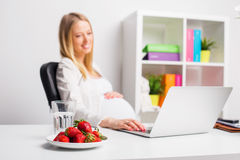 Pregnat woman at the office having strawberries. Pregnant woman at the office having strawberries and water stock images