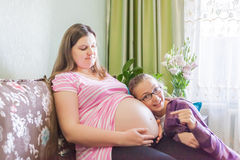 Pregnat woman resting at home with beautiful flowers stock photo
