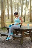 Pregnat woman taking a fitness workout rest. Pregnant woman on fitness outdoor workout rest. Pregnancy healthy lifestyle and exercise stock image