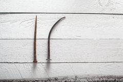 Prego oxidado no fundo de madeira branco imagem de stock
