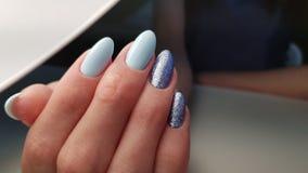 Pregos azuis do polimento do gel com brilho imagem de stock royalty free
