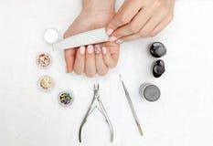 Pregos belamente manicured no desktop com as ferramentas para o tratamento de mãos fotografia de stock
