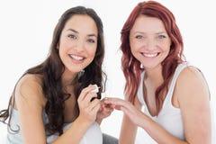 Pregos bonitos de sorriso dos amigos da pintura da jovem mulher Imagens de Stock Royalty Free