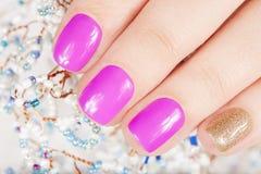 Pregos com o tratamento de mãos coberto com o rosa e o verniz para as unhas do ouro Foto de Stock