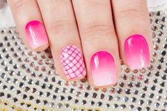 Pregos com o tratamento de mãos coberto com o verniz para as unhas cor-de-rosa Fotografia de Stock