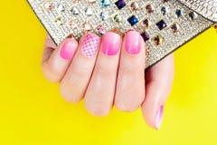 Pregos com o tratamento de mãos coberto com o verniz para as unhas cor-de-rosa, fundo amarelo Foto de Stock Royalty Free
