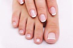 Pregos da beleza de uma mão fêmea e dos pés Fotografia de Stock Royalty Free
