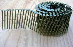 Pregos da bobina no rolo para a arma do nailer na madeira compensada imagem de stock royalty free