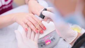 Pregos da cor da menina no salão de beleza do tratamento de mãos vídeos de arquivo