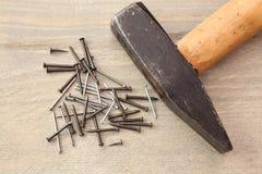 Pregos e martelo na tabela de madeira Fotografia de Stock Royalty Free