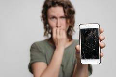 Pregos embara?ados nervosos das mordidas da menina, guardando seu smartphone quebrado imagem de stock royalty free