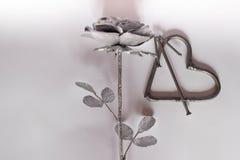 Pregos feitos a mão forjados do metal do coração em um fundo branco Rosa e coração forjados Configuração lisa, conceito mínimo da ilustração stock