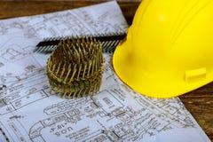 Pregos para a arma pneumática do prego e capacete para a construção um plano da casa nova fotografia de stock royalty free