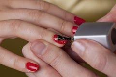 Pregos vermelhos do dedo com faíscas douradas Fotos de Stock Royalty Free