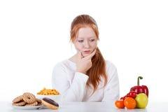 Preguntándose si comer los dulces o las verduras Imagenes de archivo