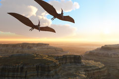 Prehistoric Canyon. Two Pterodactyl flying dinosaurs soar above a beautiful canyon Royalty Free Stock Photography