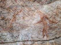 Prehistoric painting of men in actions on rock painted with red colour by human who live in the area over thousand year ago. These painting located in Phu Phra stock photography