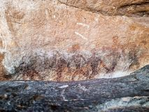 Prehistoric painting of men in actions on rock painted with red colour by human who live in the area over thousand year ago. These painting located in Phu Phra royalty free stock image