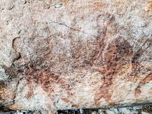 Prehistoric painting of men in actions on rock painted with red colour by human who live in the area over thousand year ago. These painting located in Phu Phra royalty free stock photography