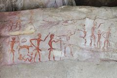 Prehistoric painting by primitive local caveman on the stone wall showing the hunting and civilization over 4000 years, Thailand royalty free stock images