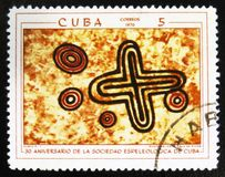 Prehistoric rock paintings, the series `The 30th Anniversary of The Cuban Speleological Society`, circa 1970. MOSCOW, RUSSIA - JULY 15, 2017: A stamp printed in royalty free stock photos