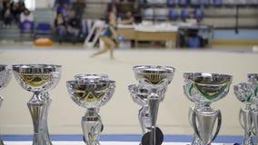 Preisschalen, rhythmische Gymnastik, unscharfe Athletenleistung im Hintergrund stock video footage