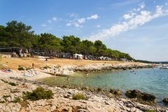 Tourists, caravans and boats on Kamenjak peninsula by the Adriatic sea in Premantura, Croatia. PREMANTURA, CROATIA - JULY 28: Tourists, caravans and boats by royalty free stock photo